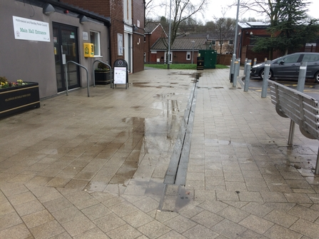 Before DePave: Puddles outside Hollinswood Neighbourhood Centre